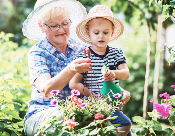 Grandmother outside gardening with grand-daughter.