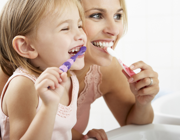 woman brushing teeth with her child