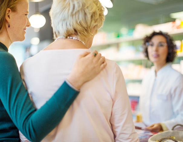 Woman and mother speaking to pharmacist