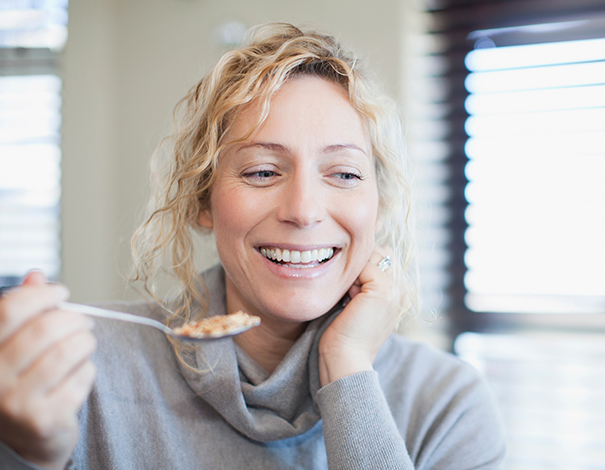 woman smiling and eating cereal